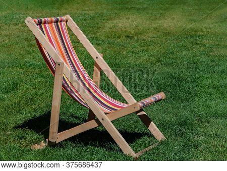 Chaise Longue Stands On Green Grass, Summer Day, Close Up