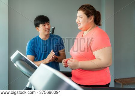 Two Asian Trainer Man And Overweight Woman Exercising Training On Treadmill In Gym, Trainer Looking