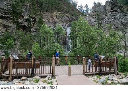 Lead, South Dakota - June 22, 2020: Tourists Admire The View Of Bridalveil Falls, A Waterfall In Spe