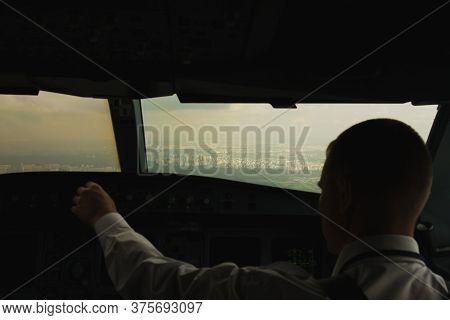 Pilot In Commercial Plane In Cockpit, Pilot Operation With Control Panel, View From The Windshield B