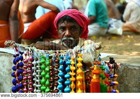 Kerala, India - December  20, 2019. An Indian Street Vendor With Colorful Thread Necklaces In Kerala