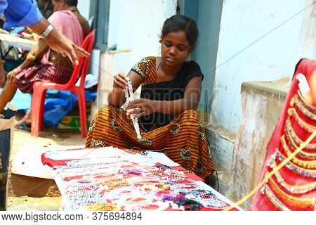Kerala, India - December 20, 2019. Child Street Vendor Girl  Attempting To Sell Colorful Beaded Neck