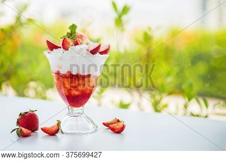 Close Up Side Views A Cup Of Delicious Strawberries Sundae With Mint Leaves On A White Table Next To
