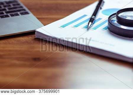 Desk With A Notebook, Report Graph Chart, Pen And Tablet On Wooden Table
