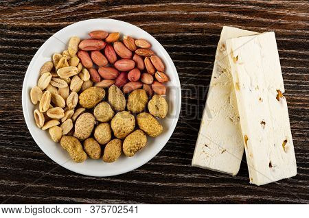 White Glass Plate With Peeled Fried Peanut, Raw Groundnuts, Peanuts In Shell, Two Nougats With Peanu