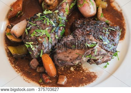 Coq Au Vin, French Chicken Braised In Red Wine, On A White Plate