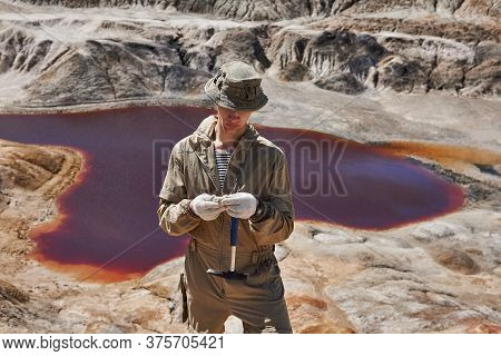 Field Expedition Geologist Examines A Sample Of A Mineral Against The Backdrop Of A Canyon With A Re