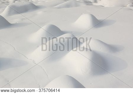A Group Of Stones Covered In Snow Lit By The Sun