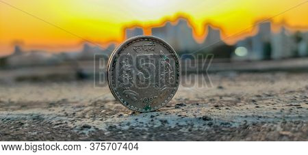 A Close-up Shot Of An Indian 5 Rupees Coin Taken In Evening Golden Shining Sunset In The City.