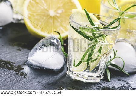 Refreshing Lemon Drink With Rosemary, Ice And Tonic, Black Stone Background, Selective Focus