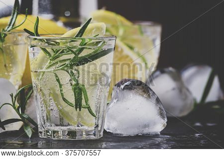 Refreshing Lemon Drink With Rosemary, Ice And Tonic, Black Stone Background, Selective Focus And Ton
