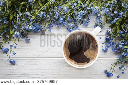 Blue Forget-me-not Flowers And A Cup Of Hot Coffee On A White Wooden Table
