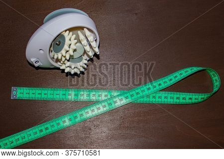Anti-cellulite Massager And Tape Measure Isolated On Dark Wooden Surface