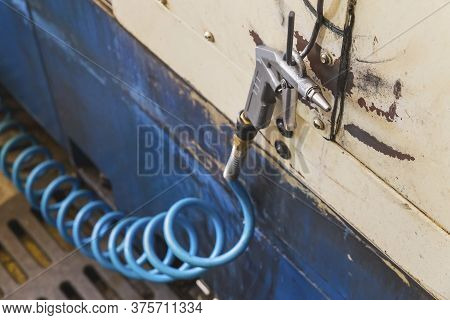 Air Gun With Blue Spiral Hose Hanging On A Metal Hook In A Workshop Foreground Focus