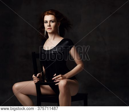 Portrait Of Elegant Sensual Tall Red-haired Woman In Black Bodysuit Underwear And Earrings Sitting O