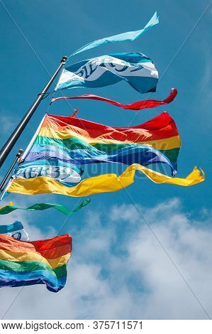 Rainbow Gay Pride Flag Fluttering On Blue Sky Background