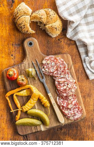 Sliced italian salami with hazelnuts, pickled chili peppers and pickles on cutting board. Top view.