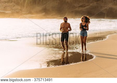 Man And Women Running On Beach At Sunset. Happy Couple Having Fun On The Coast. Couple Having Fun On