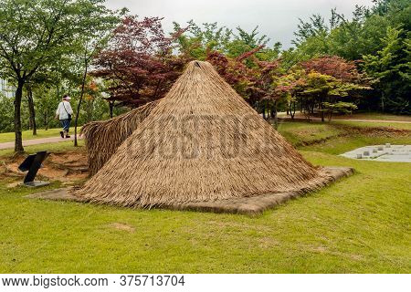 Daejeon, South Korea; July 7, 2020: Unidentified Woman Walking In Front Of Straw Thatched Hut In Pre