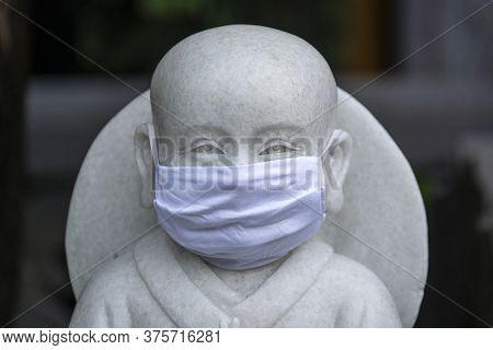 Portrait Of Buddhist Statue Wearing A Face Mask, Closeup. Concept Flu Epidemic, Coronavirus, Dust Al