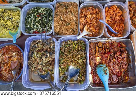 Overhead Shot Of People Buying Food Over Variety Of Delicious Malaysian Home Cooked Dishes Sold At S