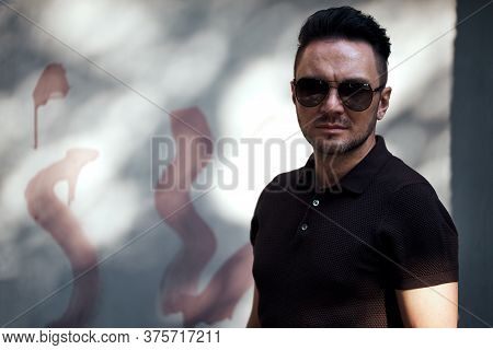 A Stylish Guy With Glasses Looks Into The Camera Against The Background Of A Spotted Fence. Strong A