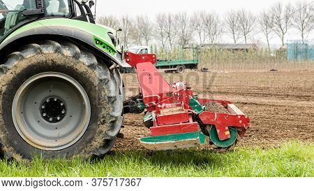 Farmer Riding A Green Tractor Plowing His Farmland With A Plowing Machine