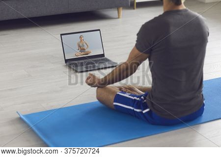 Yoga Meditation Course Online. A Man Meditates Using A Laptop Video Training Sitting On The Floor At