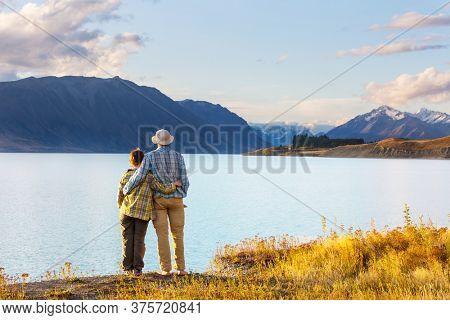 couple in beautiful mountains lake, New Zealand, Tekapo lake