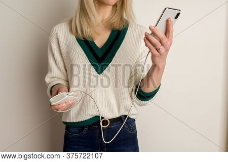 Thoughtful Girl Plays In The Phone And Infects It By Power Bank. Power Bank In Girl's Hands. Using P