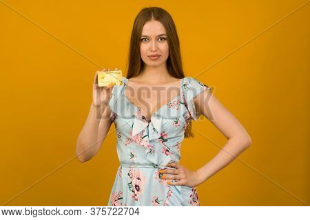 Photo Of Pleased Young Woman Posing Isolated Over Yellow Wall Background Holding Debit Or Credit Car