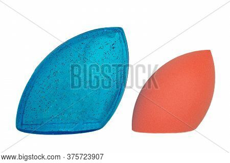 Sponge Isolated. Close-up Of A Pink Cosmetic Sponge And A Blue Plastic Package For Storage Isolated