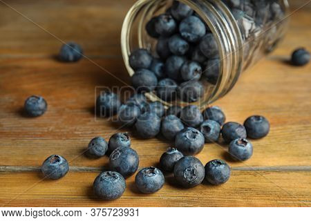 Overturned Glass Jar Of Ripe Blueberries On Wooden Table, Closeup