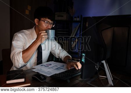 Young Pensive Asian Man Working Late Concentrated And Serious In Front Of Computer At Night In Dark