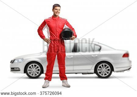 Full length portrait of a racer standing and holding a helmet in front of a silver car isolated on white background