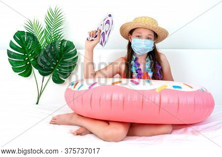 A Sad Little Girl In A Medical Mask Sits On A Bed In A Hat And Holds A Water Gun In Her Hands. Vacat