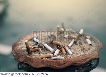 Ashtray Full Of Cigarette Butts. Used Cigarette In Ashtray. Dirty Cigarette Filter Waste In Clay Ash