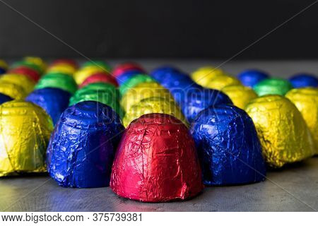 Cheap Chocolate Bonbons In Multicolored Wrapping Foil On Dark Background. Focus On Foreground With G