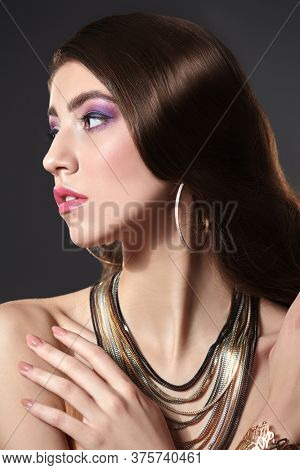 Beauty, fashion and jewellery. Portrait of a gorgeous young woman with long wavy hair posing in jewelry set on a dark background. Jewelry salon.