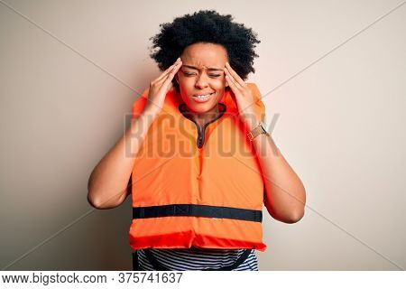 Young African American afro woman with curly hair wearing orange protection lifejacket with hand on head for pain in head because stress. Suffering migraine.