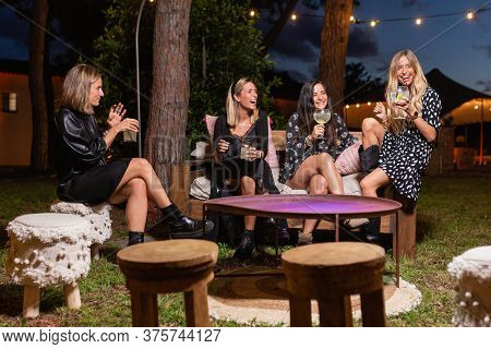 4 Caucasian Girls Dressed In Black (blondes And Brunettes) With Cups And Glasses In Their Hands With