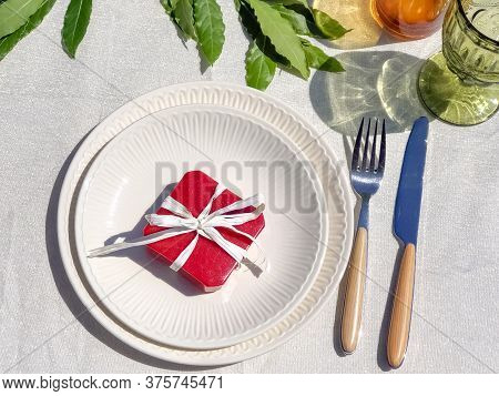 Red Gift Box With White Bow On White Plate On White Tablecloth. Gifting Concept