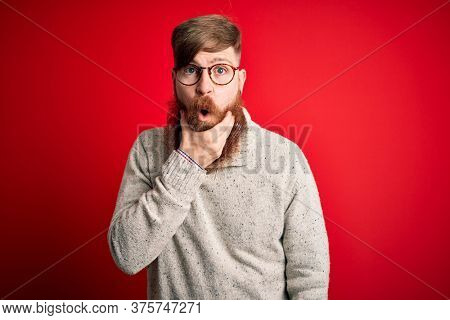 Handsome Irish redhead man with beard wearing casual sweater and glasses over red background Looking fascinated with disbelief, surprise and amazed expression with hands on chin