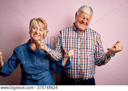 Senior beautiful couple standing together over isolated pink background very happy and excited doing winner gesture with arms raised, smiling and screaming for success. Celebration concept.