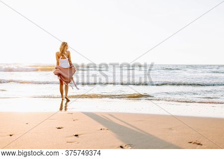 A Young Slim Girl Stands Walking On The Beach Or Ocean And Look At The Horizont. A Woman Dressed In