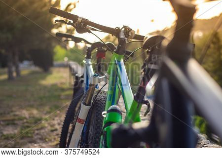 Closeup Of Mountain Bikes Standing Leaned On A Wall. Multiple Bikes, Later Afternoon Sunset Golden H