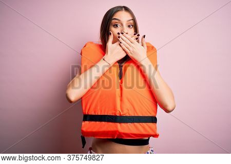 Young beautiful brunette woman wearing orange lifejacket over isolated pink background shocked covering mouth with hands for mistake. Secret concept.