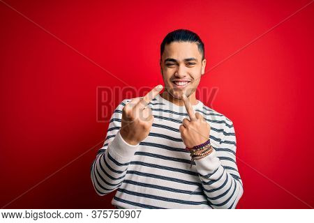 Young brazilian man wearing casual striped t-shirt standing over isolated red background Showing middle finger doing  bad expression, provocation and rude attitude. Screaming excited