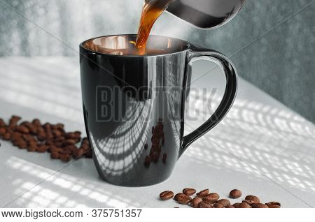 Pour Hot Coffee From The Cezve Into The Cup, Steam Rises. Against The Background Of Openwork Shadows