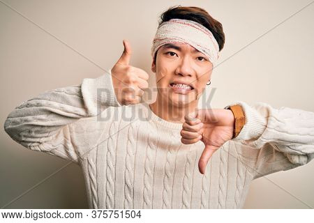 Young handsome chinese man injured for accident wearing bandage and strips on head Doing thumbs up and down, disagreement and agreement expression. Crazy conflict